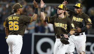 San Diego Padres' Yangervis Solarte, (26), Travis Jankowski, and Erick Aybar, from left, celebrate after the team's baseball game against the Miami Marlins in San Diego, Friday, April 21, 2017. The Padres won 5-3. (AP Photo/Christine Cotter)