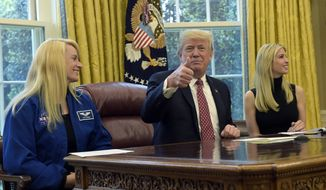 President Donald Trump, flanked by NASA astronaut Kate Rubins, left, and his daughter Ivanka Trump, gives a thumbs up following a video conference with the International Space Station, Monday, April 24, 2017, from the Oval Office of the White House in Washington. (AP Photo/Susan Walsh)