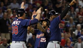 Minnesota Twins' Chris Gimenez (38), Byron Buxton (25) and Kennys Vargas, rear, celebrate scoring on a bases clearing double by Brian Dozier in the fifth inning of a baseball game against the Texas Rangers in Arlington, Texas, Monday April 24, 2017. Dozier's hit came off of Rangers starter Martin Perez. (AP Photo/Tony Gutierrez)