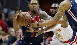 Washington Wizards guard Bradley Beal (3) catches a pass as Atlanta Hawks guard Tim Hardaway Jr. (10) defends in the first half in Game 4 of a first-round NBA basketball playoff series Monday, April 24, 2017, in Atlanta. (AP Photo/John Bazemore)