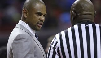 Juan Dixon, special assistant to Maryland head coach Mark Turgeon, speaks with an official in the second half of an NCAA college basketball game against Morgan State in College Park, Md., Friday, Nov. 29, 2013. (AP Photo/Patrick Semansky)