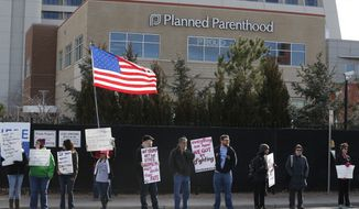Pro-choice counter-protesters hold signs supporting a woman's right to choose abortion, as nearby anti-abortion activists held a rally in front of Planned Parenthood of the Rocky Mountains in Denver on Feb. 11, 2017. (Associated Press)
