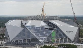 FILE -In this Tuesday, April 18, 2017 file photo, large cranes loom over the construction at the new Mercedes Benz Stadium, in Atlanta. The planned opening of the $1.5 billion stadium has been delayed. Stadium general manager Scott Jenkins told The Associated Press on Tuesday, April 25, 2017,  that the building is 90 percent done, but the biggest holdup has been roof construction. (AP Photo/Mike Stewart, File)