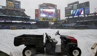 A utility vehicle anchors the tarp protecting the field as rain falls before a baseball game between the New York Mets and the Atlanta Braves, Tuesday, April 25, 2017, in New York. The game was postponed because of the weather. (AP Photo/Kathy Willens)