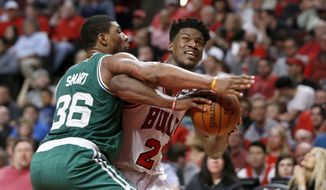 Chicago Bulls' Jimmy Butler (21) is pressured by Boston Celtics' Marcus Smart during the second half in Game 4 of an NBA basketball first-round playoff series in Chicago, Sunday, April 23, 2017. The Celtics won 104-95. (AP Photo/Charles Rex Arbogast)