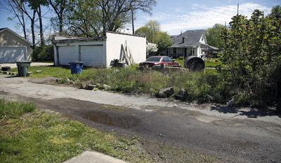 This Tuesday, April 25, 2017 photo shows the area where a man was mauled to death by a dog in the alley early Tuesday in Dayton, Ohio. Lt. Mark Ponichtera said police found the man being attacked in an alley. They were able to get the dog to back off, and the man was taken to a hospital, where he died.  Police fatally shot the dog, which they say was a pit bull. They were trying to determine its owner.   (Ty Greenlees/Dayton Daily News via AP)