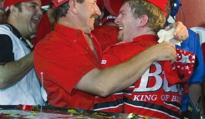 FILE - In this May 20, 2000, file photo, Dale Earnhardt, left, embraces his son Dale Earnhardt Jr, right, in victory lane after Dale Earnhardt Jr won The Winston All-Star auto race at Lowe's Motor Speedway in Concord, N.C. Dale Earnhardt Jr. abruptly announced his retirement at the end of the season Tuesday, April 25, 2017, a decision that will cost NASCAR its most popular driver as the series scrambles to rebuild its fan base. (AP Photo/Chuck Burton, File)