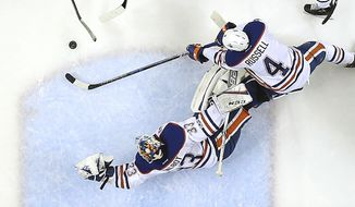 Edmonton Oilers goalie Cam Talbot (33) and teammate defenseman Kris Russell (4) block a shot at goal by San Jose Sharks center Logan Couture (39) during the second period in Game 6 of a first-round NHL hockey playoff series Saturday, April 22, 2017, in San Jose, Calif. The Oilers won 3-1. (AP Photo/Tony Avelar)