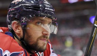 FILE - In this Tuesday, March 14, 2017, file photo, Washington Capitals left wing Alex Ovechkin (8), of Russia, looks on from the bench during the first period of an NHL hockey game against the Minnesota Wild in Washington. To get to their first Eastern Conference final in the past decade, Alex Ovechkin and the Washington Capitals will have to go through the Sidney Crosby and Pittsburgh Penguins, who have quite simply had their number in the playoffs. (AP Photo/Nick Wass, File)