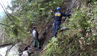 FILE - In this undated photo provided by the National Transportation Safety Board, investigators work near the wreckage of a sightseeing plane that crashed, Thursday, June 25, 2015, in remote, mountainous terrain near Ketchikan in southeast Alaska, killing the pilot and eight passengers. The NTSB on Tuesday, April 25, 2017, said the pilot's decision to fly using visual flight rules when conditions called for instrument rules was a cause of a fatal crash of the sightseeing flight. (National Transportation Safety Board via AP, File)