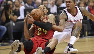 Washington Wizards guard Bradley Beal, right, battles for the ball against Atlanta Hawks forward Kent Bazemore (24) during the first half in Game 5 of a first-round NBA basketball playoff series, Wednesday, April 26, 2017, in Washington. (AP Photo/Nick Wass)
