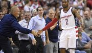 Washington Wizards guard John Wall (2) slaps hands with a fan during the second half in Game 5 of the team's first-round NBA basketball playoff series against the Atlanta Hawks, Wednesday, April 26, 2017, in Washington. The Wizards won 103-99. (AP Photo/Nick Wass)