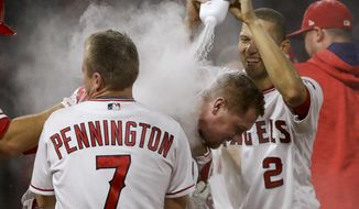 Los Angeles Angels' Kole Calhoun, center, celebrates his game-winning hit with teammates during the 11th inning of a baseball game against the Oakland Athletics in Anaheim, Calif., Tuesday, April 25, 2017. The Angels won 2-1. (AP Photo/Chris Carlson)