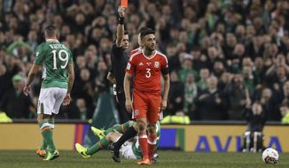 FILE - In this file photo dated March 24, 2017,  Wales' Neil Taylor is sent off for a red card tackle which broke the right leg of Ireland captain Seamus Coleman during the Republic of Ireland v Wales World Cup qualifier.  FIFA announced Wednesday April 26, 2017, that Taylor is banned for two World Cup qualifying games for the red-card tackle that broke the leg of an Ireland opponent. (Brian Lawless/PA via AP)