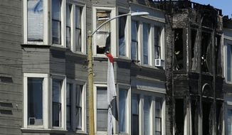 FILE - In this March 28, 2017 file photo sheets of linen are seen tied together hanging from a window to form an escape ladder at the site of a four alarm apartment fire, in Oakland, Calif. Residents of the troubled, low-income apartment building that caught fire and killed four in Northern California last month have filed a lawsuit against the building's owners and managers, accusing them of ignoring numerous fire code violations. (AP Photo/Ben Margot, File)