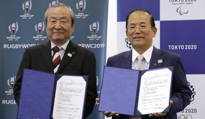Tokyo 2020 Olympics CEO Toshiro Muto, right, and President and CEO of the 2019 Rugby World Cup Organizing Committee President and CEO Akira Shimazu show documents signed a collaborative agreement in Tokyo, Wednesday, April 26, 2017. Organizers of the 2020 Olympics signed a collaborative agreement with the organizers of the 2019 Rugby World Cup, aiming to maximize the benefits and impact of the global events. The Rugby World Cup will be staged in Japan as Tokyo is finalizing preparations to host the Summer Games for the first time since 1964. (AP Photo/Eugene Hoshiko)