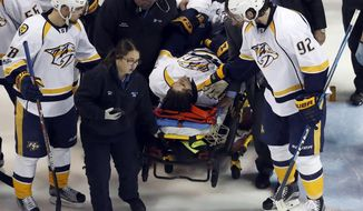 Nashville Predators' Ryan Johansen (92) and Viktor Arvidsson, left, of Sweden, offer encouragement to teammate Kevin Fiala, of Switzerland, as Fiala is taken off on a stretcher after being injured during the second period in Game 1 of an NHL hockey second-round playoff series against the St. Louis Blues, Wednesday, April 26, 2017, in St. Louis. (AP Photo/Jeff Roberson)