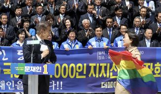 A protester holding a rainbow flag, approaches South Korea's presidential candidate Moon Jae-in from the Democratic Party, left, at National Assembly in Seoul, South Korea, Wednesday, April 26, 2017. South Korean presidential front-runner Moon Jae-in has outraged persecuted sexual minority groups by saying during a television debate that he opposes homosexuality. (Ahn Jung-won/Yonhap via AP)