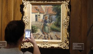 """FILE - In this Feb. 8, 2014, file photo, a visitor to the Fred Jones Jr. Museum of Art at the University of Oklahoma in Norman, Okla., takes a photograph of a piece called """"Shepherdess Bringing in Sheep"""" by French impressionist artist Camille Pissarro, at the museum. The 1886 painting that was stolen as part of a Nazi looting campaign that stretched across Europe during World War II has transferred from the University of Oklahoma to Paris and will be on display at the French museum, Musee d'Orsay, for five years before returning to the university in alternating three-year intervals. (AP Photo/Sue Ogrocki, File)"""
