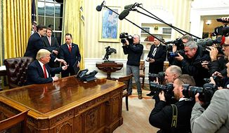 President Trump hands over his pen after signing his first executive order on Jan. 20, surrounded by the press. (AP Photo/Evan Vucci)