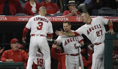 Los Angeles Angels' Danny Espinosa (3) is greeted by Mike Trout, center, Kole Calhoun, right, and manager Mike Scioscia, left, after he scored on a single by Cameron Maybin during the second inning of a baseball game against the Oakland Athletics, Wednesday, April 26, 2017, in Anaheim, Calif. (AP Photo/Jae C. Hong)