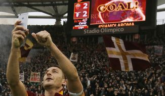 """FILE - In this Sunday, Jan. 11, 2015 file photo, Roma's Francesco Totti celebrates with a selfie after scoring during a Serie A soccer match between Roma and Lazio at Rome's Olympic stadium. Roma great Francesco Totti wants """"to destroy"""" Lazio in what could be his last ever derby on Sunday. (AP Photo/Gregorio Borgia, File)"""
