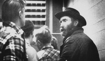 """FILE - In this Dec. 14, 1984, file photo, fugitive Don Nichols, right, is lead into custody along with his son, Dan Nichols, after their capture several hours earlier near the Bear Trap Canyon about 30 miles west of Bozeman, Mont. The two men were charged with homicide, kidnapping, aggravated assault and intimidation for the kidnapping of Bozeman biathlete Kari Swenson and the murder of Alan Goldstein on July 16, 1984. Self-described """"mountain man"""" Don Nichols was granted parole Thursday, April 27, 2017, after serving nearly 32 years for kidnapping the work class athlete on a training run in July 1984 and killing her would-be rescuer. (AP Photo, File)"""