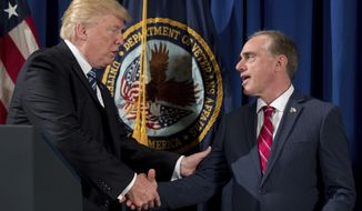 """President Donald Trump shakes hands with Veterans Affairs Secretary David Shulkin, right, as he prepares to sign an Executive Order on """"Improving Accountability and Whistleblower Protection"""" at the Department of Veterans Affairs, Thursday, April 27, 2017, in Washington. (AP Photo/Andrew Harnik)"""