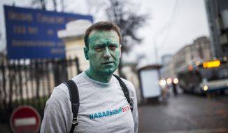 In this photo taken on Thursday, April 27, 2017, Russian opposition leader Alexei Navalny poses for a photo after unknown attackers doused him with green antiseptic, outside a conference venue in Moscow, Russia. Navalny, who authored a documentary about the Russian prime minister's alleged corrupt wealth that was viewed more than 20 million times online, was the key force behind nationwide anti-government rallies in March, Russia's largest and most widespread in years. (Evgeny Feldman/Pool Photo via AP)