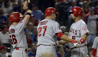 Los Angeles Angels' Kole Calhoun (56), Mike Trout (27) and Albert Pujols, right, celebrate the three-run home run by Pujols that came off a pitch from Texas Rangers relief pitcher Jeremy Jeffress in the eighth inning of a baseball game in Arlington, Texas, Friday, April 28, 2017. (AP Photo/Tony Gutierrez)