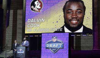 Former Minnesota Vikings player John Randle, right, announces Florida State's Dalvin Cook as the Vikings selection in the second round of the 2017 NFL football draft as NFL commissioner Roger Goodell stands by, Friday, April 28, 2017, in Philadelphia. (AP Photo/Matt Rourke)