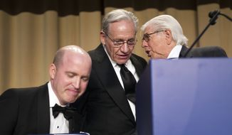 White House Correspondents' President Jeff Mason, White House correspondent for Reuters, left, sits in his chair while journalists Bob Woodward, center, and Carl Bernstein talk during the association's dinner in Washington, Saturday, April 29, 2017. (AP Photo/Cliff Owen)