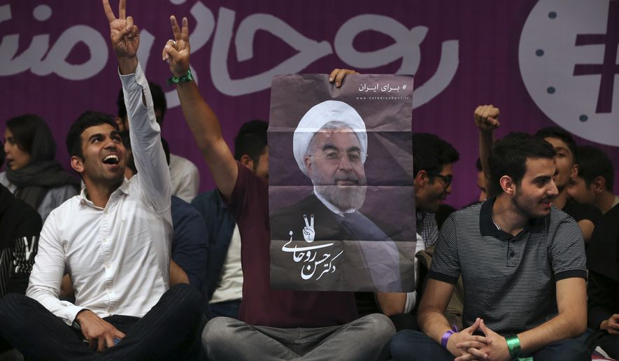 Pro-reform Iranian youths who support President Hassan Rouhani for the May 19 presidential election flash the victory sign as one of them holds Rouhani's poster in a campaign rally in Tehran, Iran, Saturday, April, 29, 2017. Rouhani, Iran's president since 2013, is running for a second term in office. (AP Photo/Vahid Salemi)