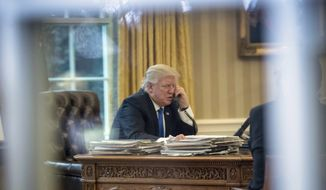 DAY 9 - In this Jan. 28, 2017, file photo, President Donald Trump speaks on the phone with German Chancellor Angela Merkel in the Oval Office at the White House in Washington. (AP Photo/Andrew Harnik, File)
