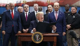President Donald Trump reads from an Executive Order on the Establishment of Office of Trade and Manufacturing Policy at The AMES Companies, Inc., in Harrisburg, Pa., Saturday, April, 29, 2017. Behind the president from left are Vice President Mike Pence, Secretary of Veterans Affairs David Shulkin, and Commerce Secretary Wilbur Ross. (AP Photo/Carolyn Kaster)