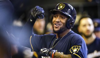 Milwaukee Brewers' Domingo Santana is greeted by teammates in the dugout after hitting a two-run home run, his second of the game, off Atlanta Braves' Mike Foltynewicz during the sixth inning of a baseball game Sunday, April 30, 2017, in Milwaukee. (AP Photo/Tom Lynn)