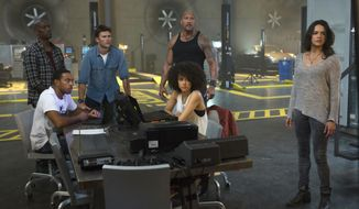 """This image released by Universal Pictures shows, Chris """"Ludacris"""" Bridges, seated left, and Nathalie Emmanuel, seated right, and Tyrese Gibson, standing from left, Scott Eastwood, Dwayne Johnson and Michelle Rodriguez in """"The Fate of the Furious."""" (Matt Kennedy/Universal Pictures via AP)"""