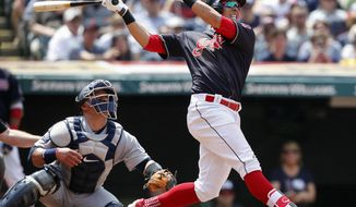 Cleveland Indians' Michael Brantley watches his two-run home run as Seattle Mariners catcher Carlos Ruiz looks on during the third inning in a baseball game, Sunday, April 30, 2017, in Cleveland. (AP Photo/Ron Schwane)