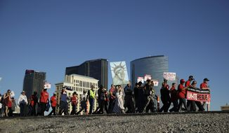 People walk along a road during a May Day march Monday, May 1, 2017, in Las Vegas. Union members and activists marched along and near the Las Vegas Strip to highlight immigration issues and push back against Trump administration policies. (AP Photo/John Locher)