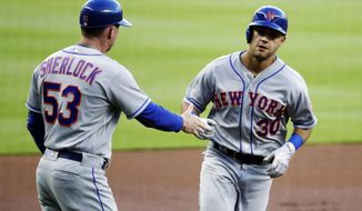 New York Mets' Michael Conforto, right, is congratulated by third base coach Glenn Sherlock after hitting a home run in the first inning of a baseball game against the Atlanta Braves in Atlanta, Monday, May 1, 2017. (AP Photo/David Goldman)