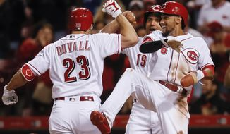 Cincinnati Reds' Adam Duvall (23) celebrates with Billy Hamilton (6) and Joey Votto (19) after hitting a three-run home run off Pittsburgh Pirates starting pitcher Gerrit Cole in the sixth inning of a baseball game, Monday, May 1, 2017, in Cincinnati. (AP Photo/John Minchillo)