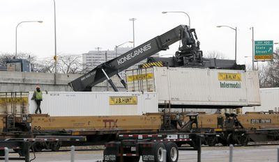 """FILE - In this Feb. 21, 2017 file photo, containers are unloaded from a rail car in the Norfolk Southern rail yard in Chicago. Chicago aldermen representing high-crime neighborhoods near a Norfolk Southern rail yard where thieves in recent years stole over 100 guns want new laws aimed at ensuring railways properly secure the facilities. An ordinance they recently introduced notes a """"vice grip of gun violence"""" and contends city """"train yards have emerged as a ready source of firearms."""" Among other things, it would mandate rail-yard fences be well maintained. (AP Photo/Charles Rex Arbogast, File)"""