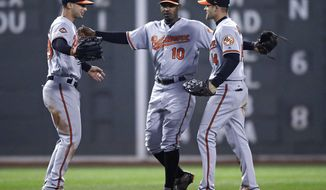 Baltimore Orioles center fielder Adam Jones (10) celebrates with right fielder Craig Gentry, right, and left fielder Joey Rickard left, after defeating the Boston Red Sox 5-2 during a baseball game at Fenway Park in Boston, Monday, May 1, 2017. (AP Photo/Charles Krupa)