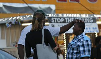 Darin Fontenette, left, football coach for Na'Quincy Pierson, son of Alton Sterling, pats Na'Quincy on the head outside the Triple S Food Mart, where Sterling was killed last year in Baton Rouge, La., Tuesday, May 2, 2017. The U.S. Justice Department has decided not to charge two white Baton Rouge police officers in the death of Sterling, whose death was captured on cell phone video, fueling protests in Louisiana's capital and beyond. (AP Photo/Gerald Herbert)