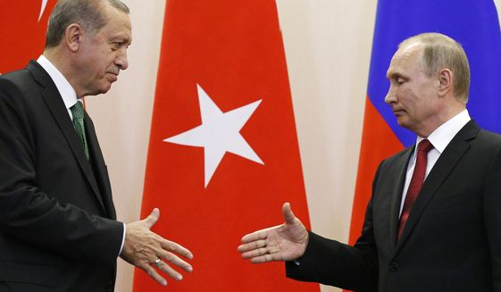 Russian President Vladimir Putin, right, and Turkish President Recep Tayyip Erdogan reach out to shake hands after a news conference following their talks in Putin's residence in the Russian Black Sea resort of Sochi, Russia, Wednesday, May 3, 2017. The presidents of Russia and Turkey are holding talks on the situation in Syria and also the restoration of full economic ties between their two countries. (AP Photo/Alexander Zemlianichenko, Pool)