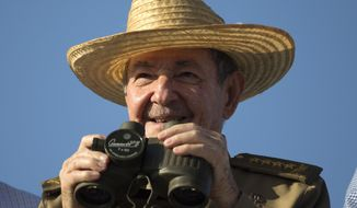 Cuba's President Raul Castro uses binoculars to watch the May Day march at Revolution Square in Havana, Cuba, Monday, May 1, 2017. (AP Photo/Desmond Boylan)