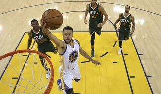 Golden State Warriors' Stephen Curry (30) drives to the basket past Utah Jazz's Joe Johnson, left, Rudy Gobert (27) and George Hill (3) during the second half in Game 1 of an NBA basketball second-round playoff series, Tuesday, May 2, 2017, in Oakland, Calif. (Ezra Shaw/Pool Photo via AP)