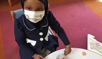 In this Tuesday, May 2, 2017, photo, Amira Hassan, of Burnsville, Minn., plays in the waiting room at the specialty clinic at Children's Minnesota in Minneapolis. Hassan went to the hospital's clinic for a routine wellness check, but had to wear a mask to protect her from measles after an outbreak has sickened more than 30 children in Minnesota. The masks are just one precaution that hospitals are taking to try to control the spread of the disease, which is predominantly affecting Minnesota's Somali community. (AP Photo/Amy Forliti)