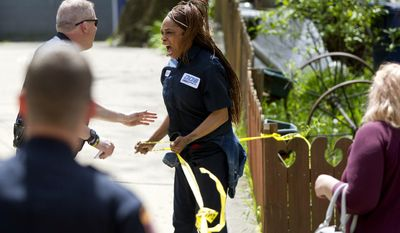 A woman reacts after Grand Rapids Police shot an 18-year-old man Wednesday, May 3, 2017, in Grand Rapids, Mich.  The man reportedly fired on police and they returned fire, wounding him. The woman identified herself as the man's mother. (Cory Morse /The Grand Rapids Press via AP)