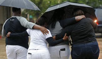 Cameron Sterling, left, son of Alton Sterling, hugs family members after they spoke to reporters following a meeting with the U.S. Justice Department at federal court in Baton Rouge, La., Wednesday, May 3, 2017. The Justice Department has decided not to charge two white Baton Rouge police officers in the shooting death of Sterling. (AP Photo/Gerald Herbert)